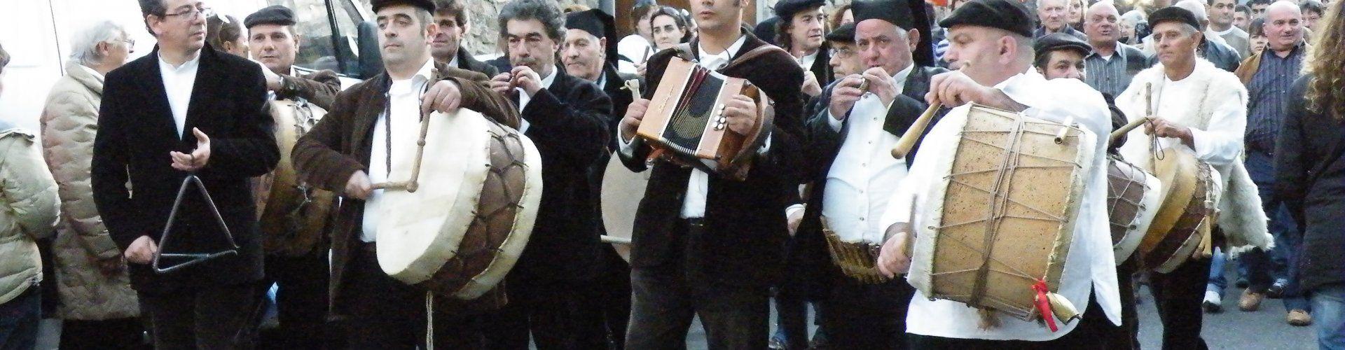 Männer in dunklen Samtanzügen, weißen Hemden und mit sardischen Berittas spielen traditionelle Instrumente beim Orangenfest in Muravera