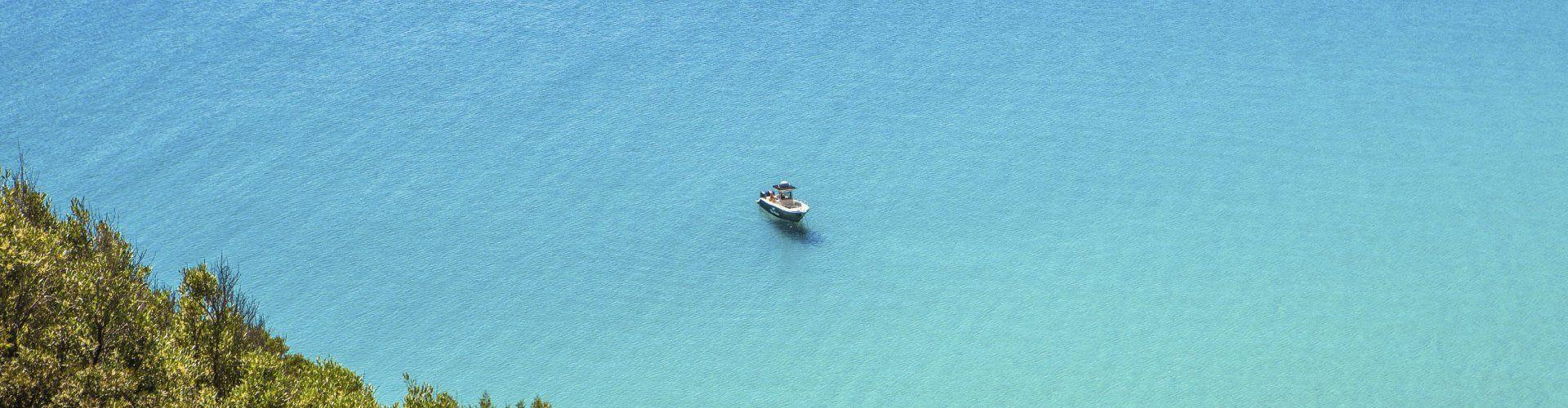 Blaues Meer mit darauf schwimmendem Motorboot, Torre delle Stelle