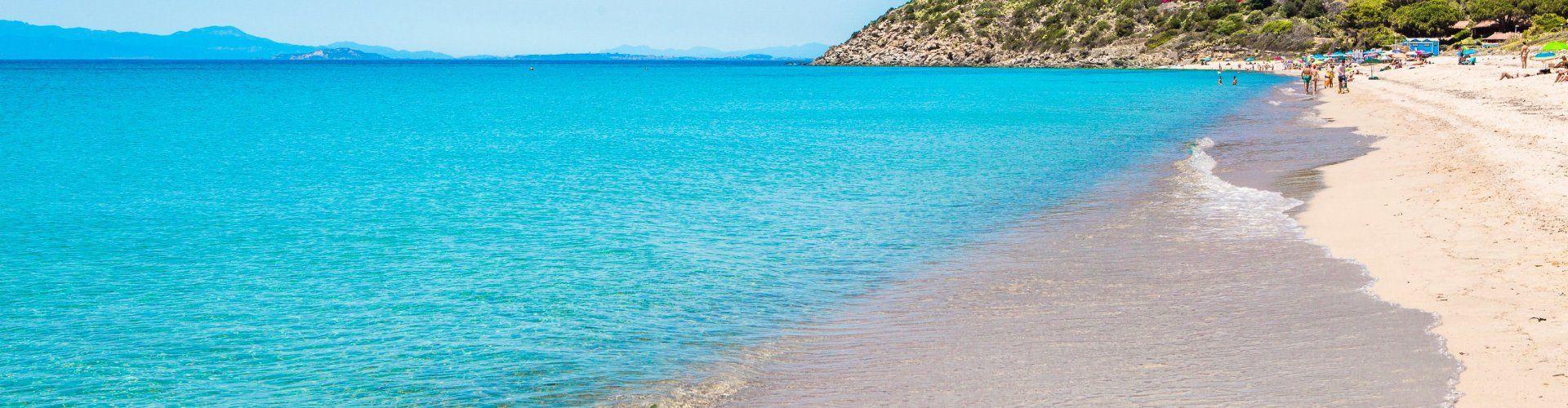 Strand Geremeas mit glasklarem Wasser und Torre delle Stelle im Hintergrund