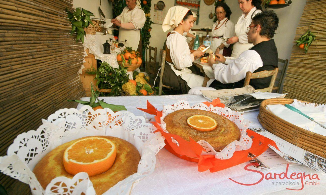 Präsentation von Orangenkuchen beim Tag der offenen Tür, im Zimmer dahinter Sarden in Trachten bei der Zubereitung der Kuchen