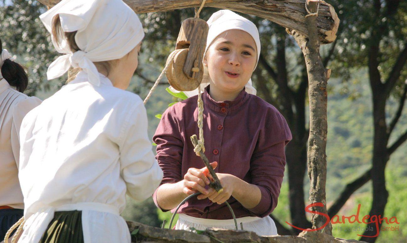 Mädchen in sardischer Tracht holen Wasser aus einem alten Brunnen