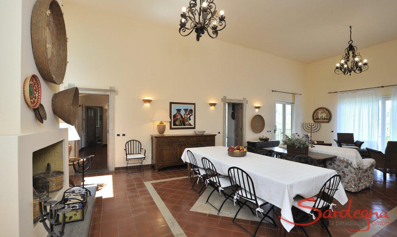 Sardisch eingerichtetes Wohnzimmer mit großem Esstisch und Kamin
