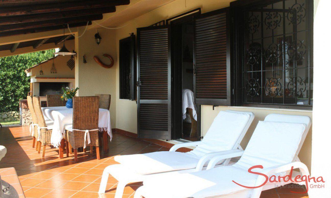 Großflächige Terrasse mit Sonnenliegen und Esstisch