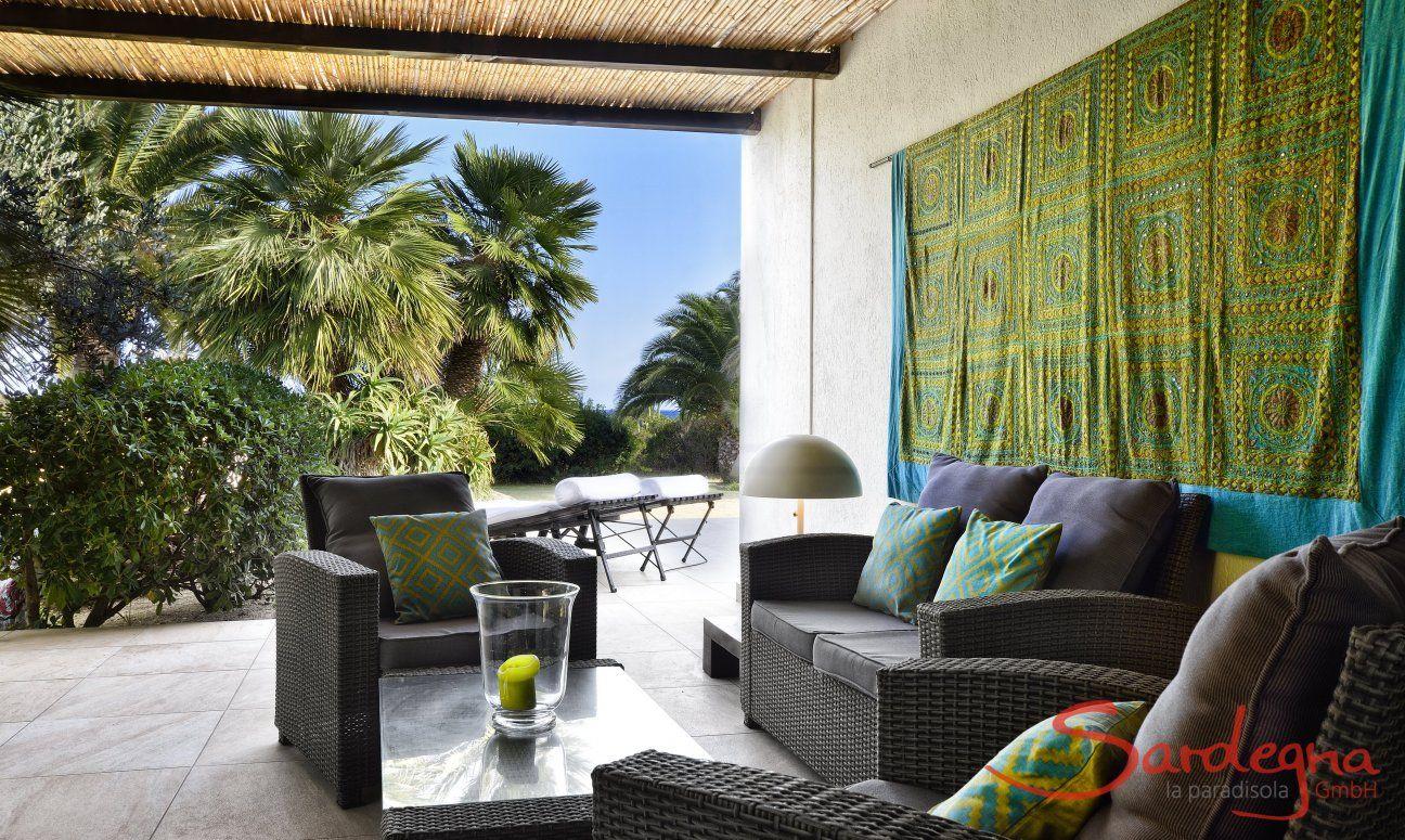 Überdachter Loungebereich außen mit Blick auf den Garten
