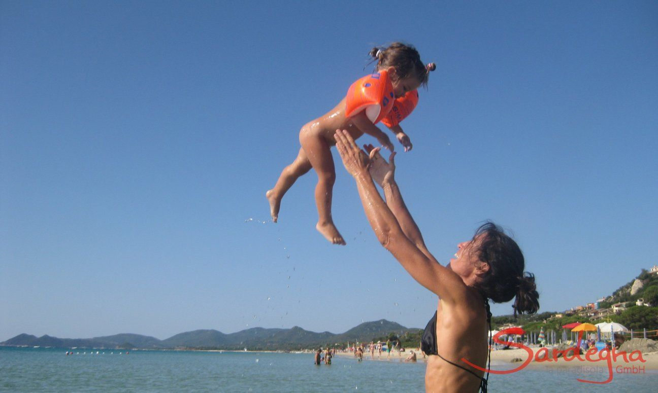 Mutter wirft ihr Baby in die Luft am Meer bei Monte Nai