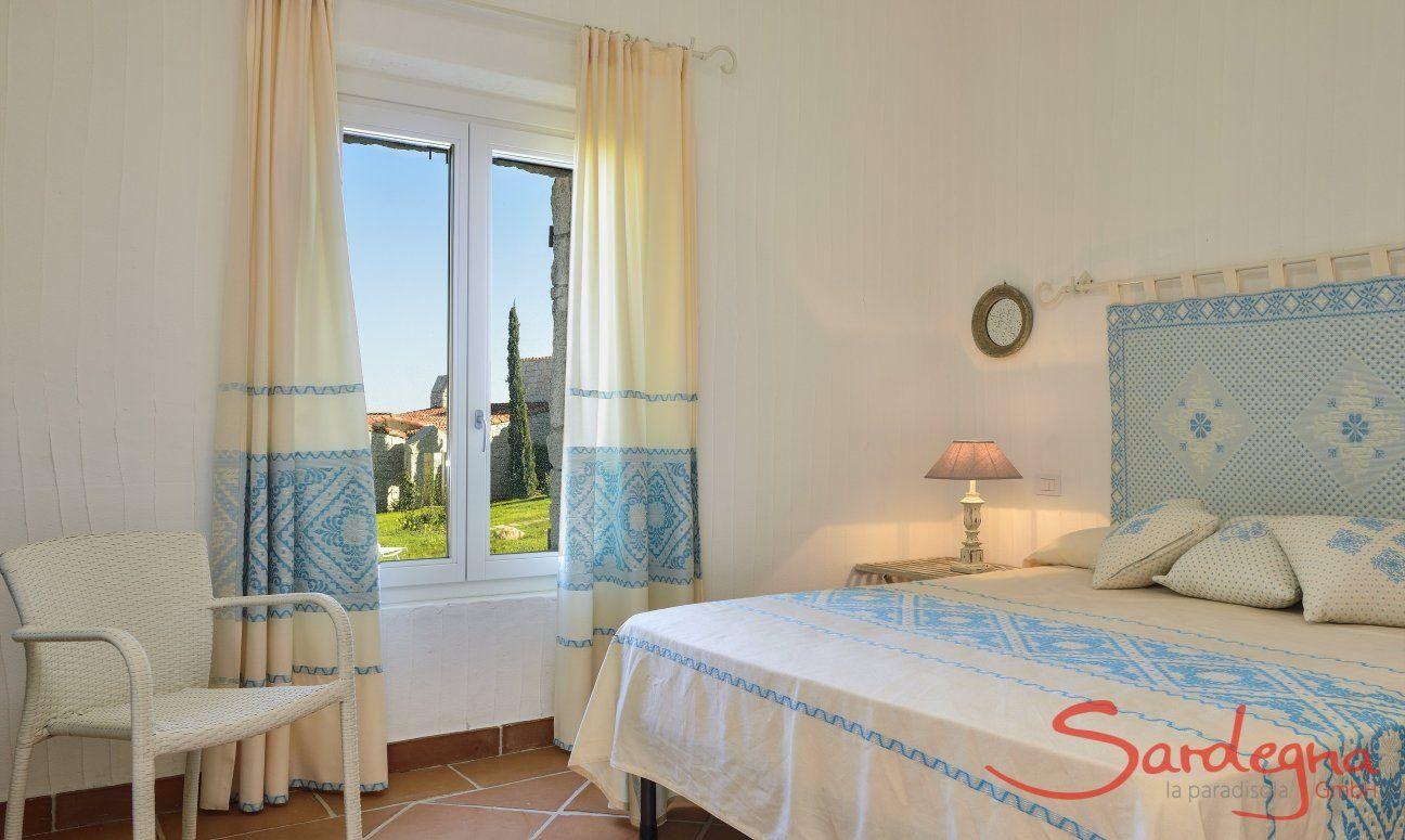 Schlafzimmer mit Doppelbett mit hellblau dekorierten sardischen Stoffen Li Conchi 9, Cala Sinzias