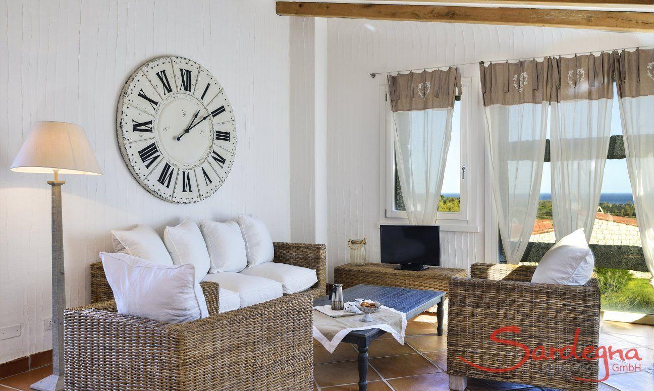 Sofa vor großer Wanduhr und Panoramafenster Li Conchi 9, Cala Sinzias
