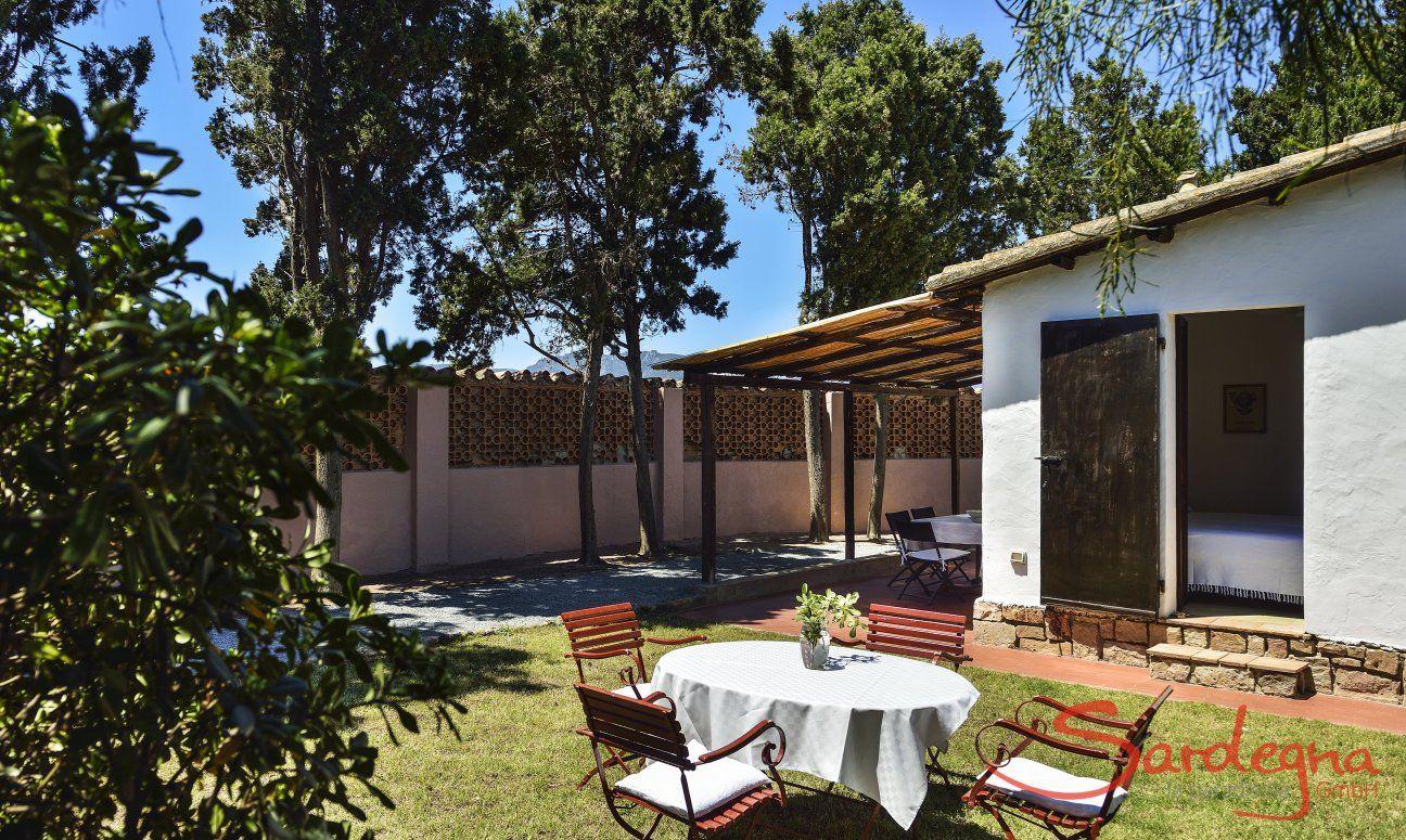 Blick auf Garten mit Eßtisch, Haus und Mauer von Su Faru
