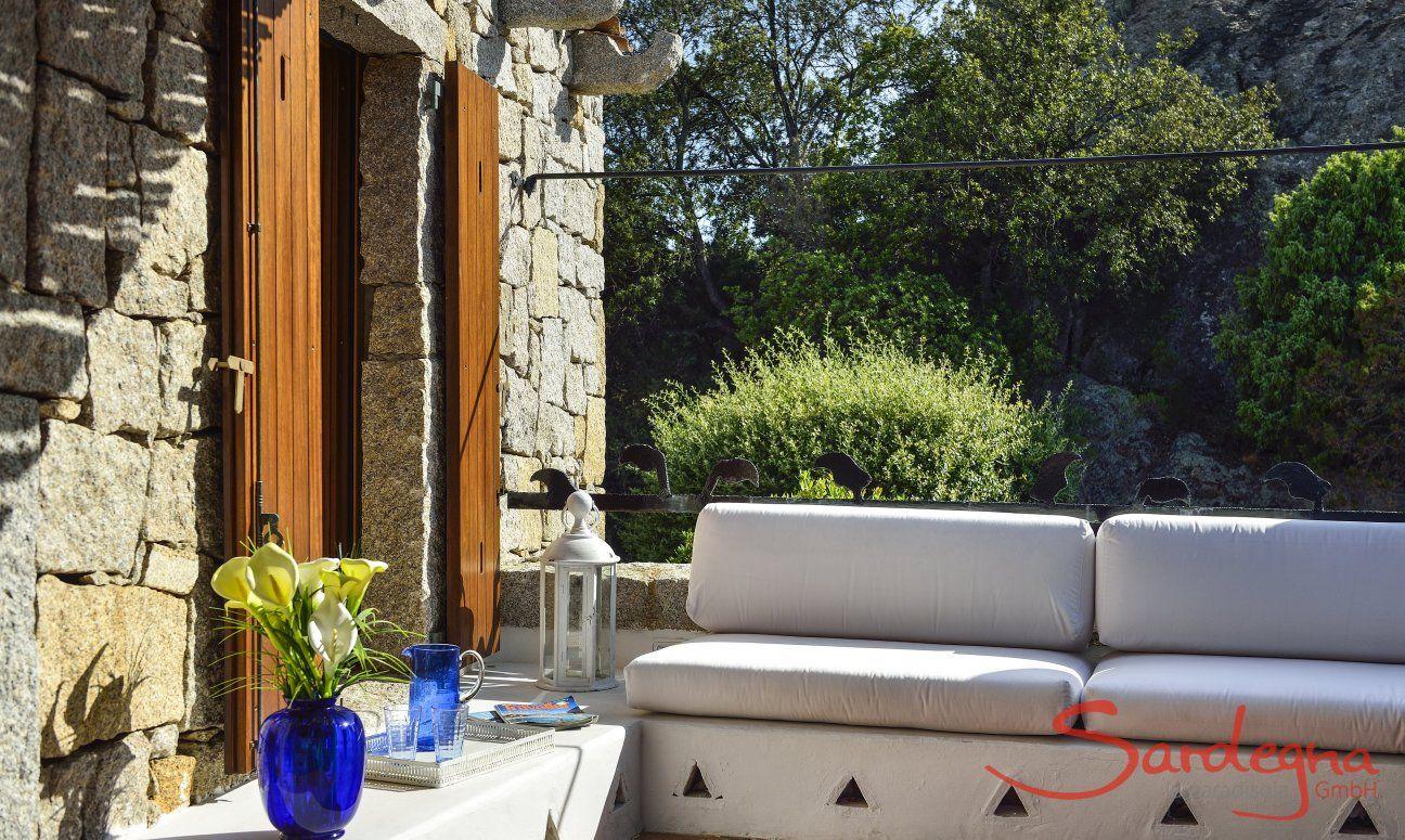Gemauerte Sitzbank vor grüner Natur und Granitfelsen der Costa Smeralda