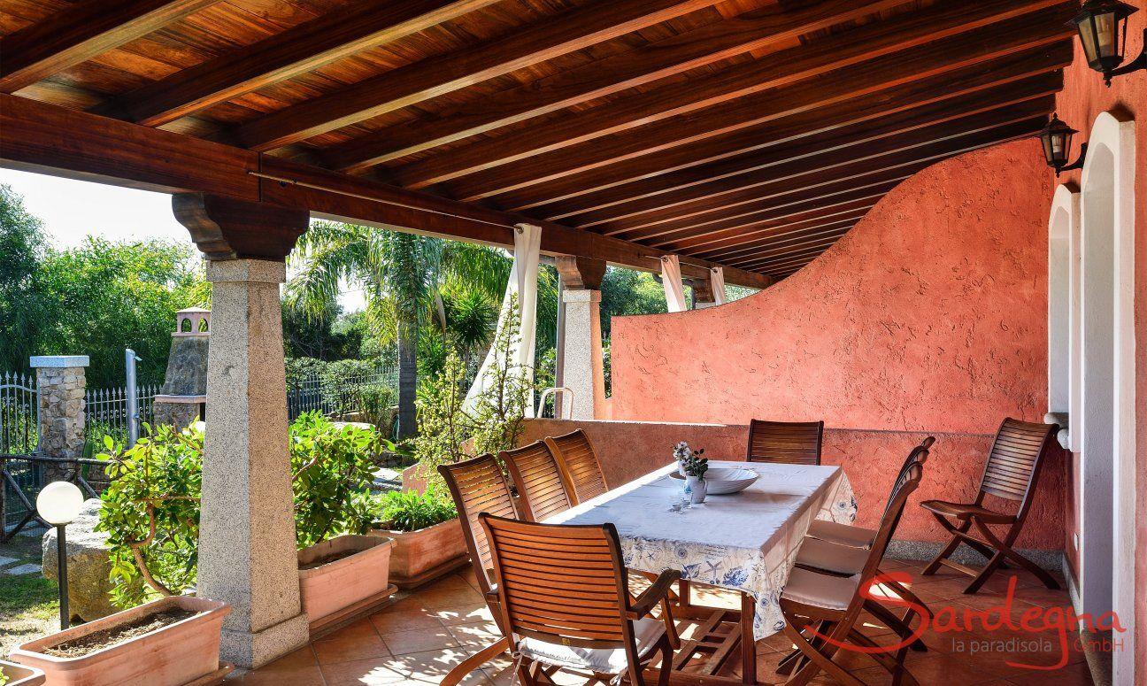 Überdachte Terrasse mit Esstisch im Freien