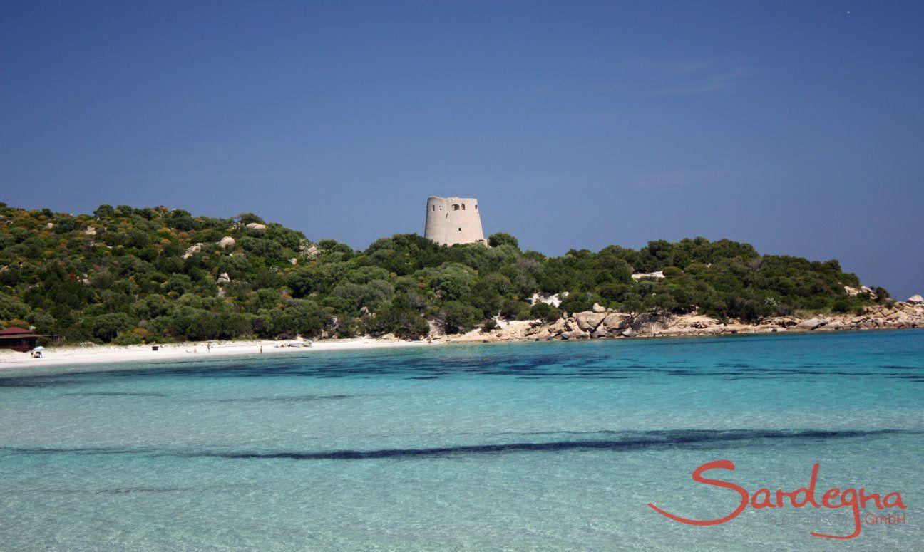Glasklares Meer, weißer Strand und spanischer Wachtrum in der Bucht Cala Pira