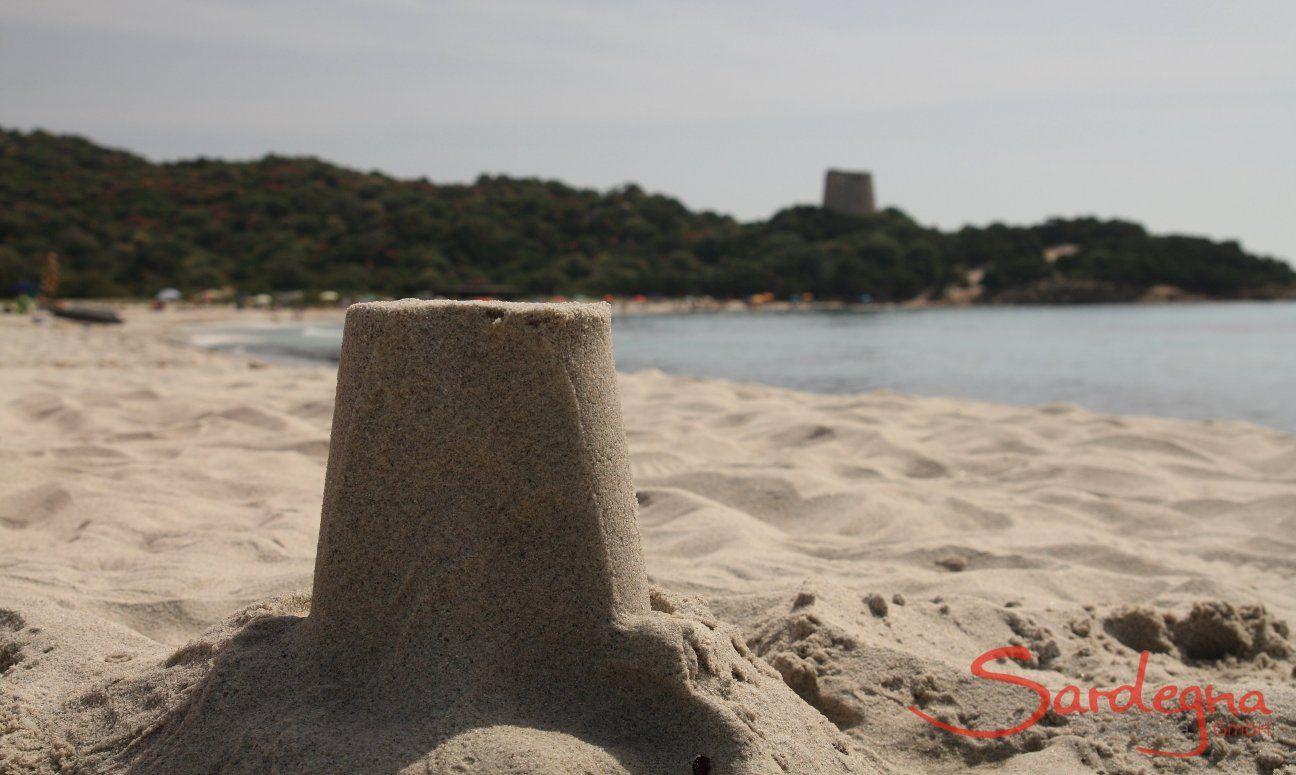 Mit Sand nachgebauter spanischer Wachturm von Cala Pira im Vordergrund, im Hintergrund der echte Turm