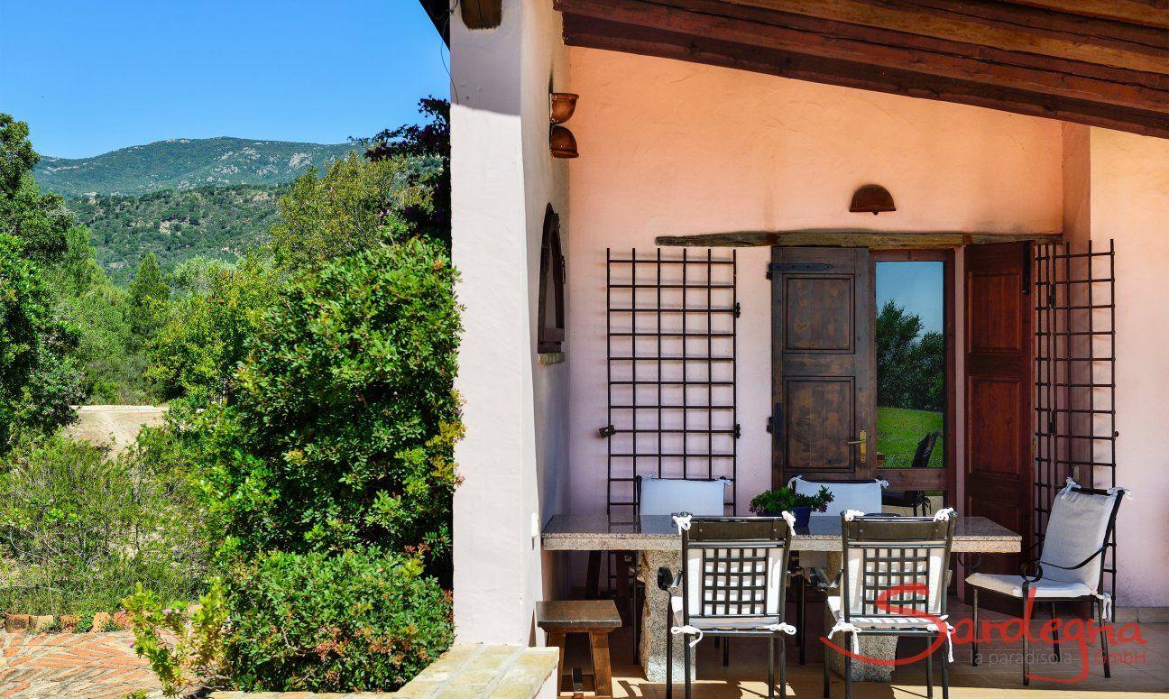 Überdachte Terrasse mit rusitkalem Granittisch und Zugang zum Wohnbereich