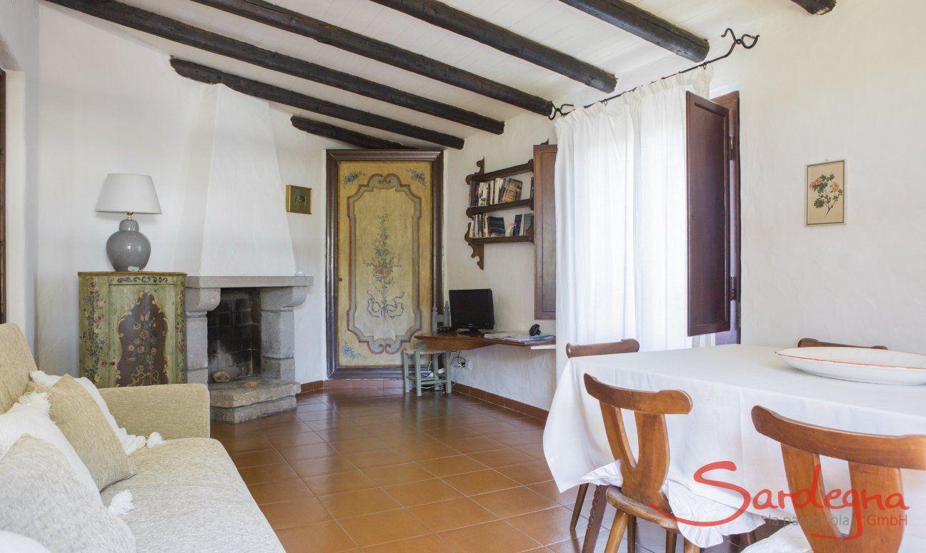 Sardisch eingerichtetes Wohnzimmer mit Esstisch und Kamin