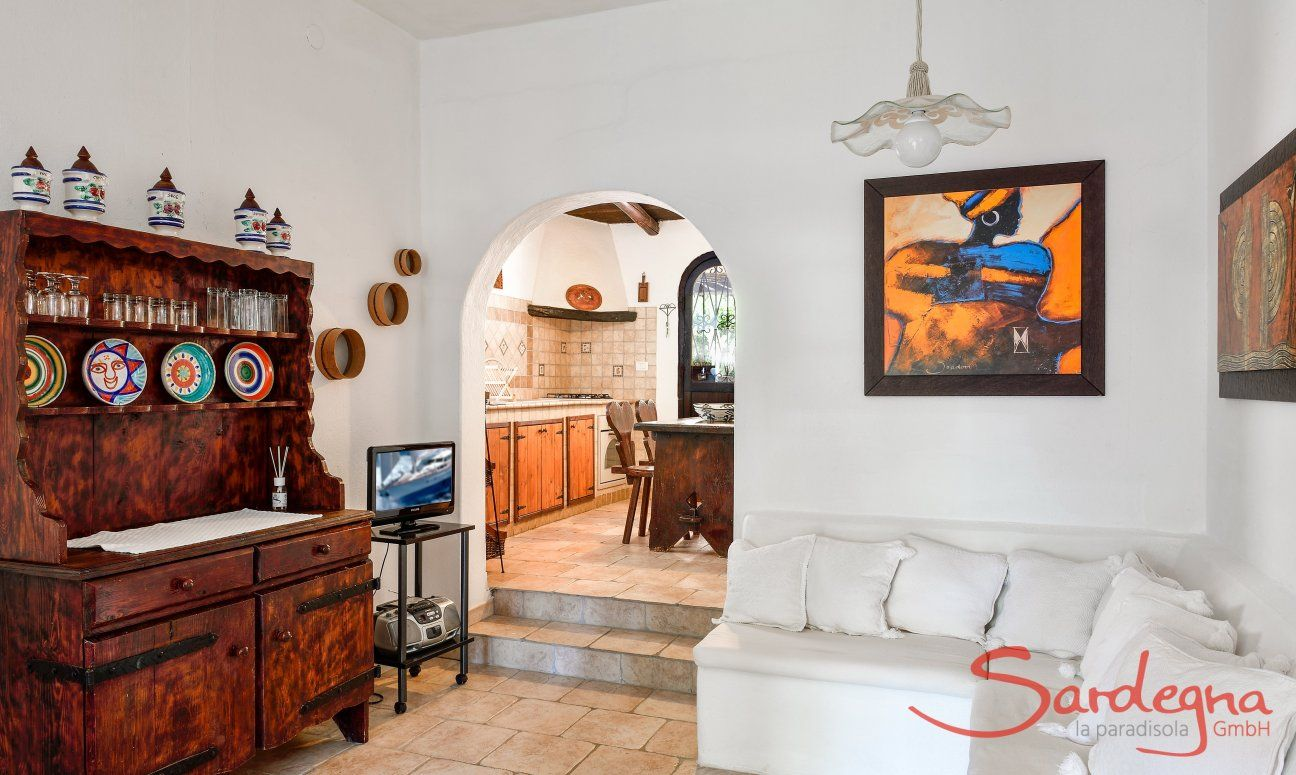 Wohnzimmer mit gemauerter Sitzbank und Rundbogen zur Küche