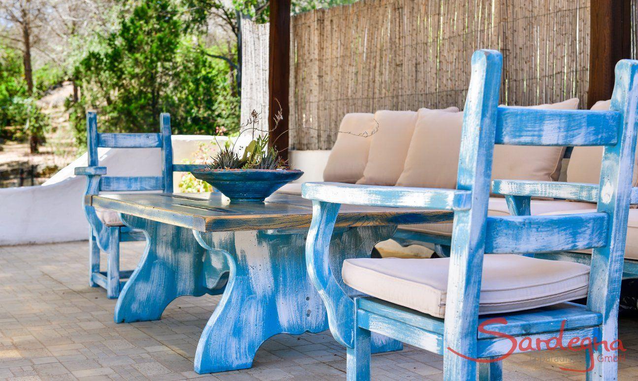 Terrasse mit rustikaler Sitzgruppe aus Holz in sardischem Stil