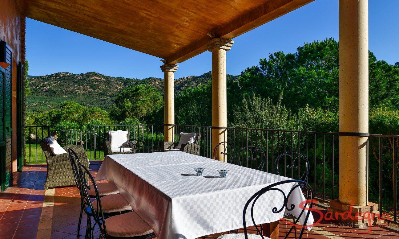 Terrasse Westflügel mit großem Esstisch und Lounge-Möbeln