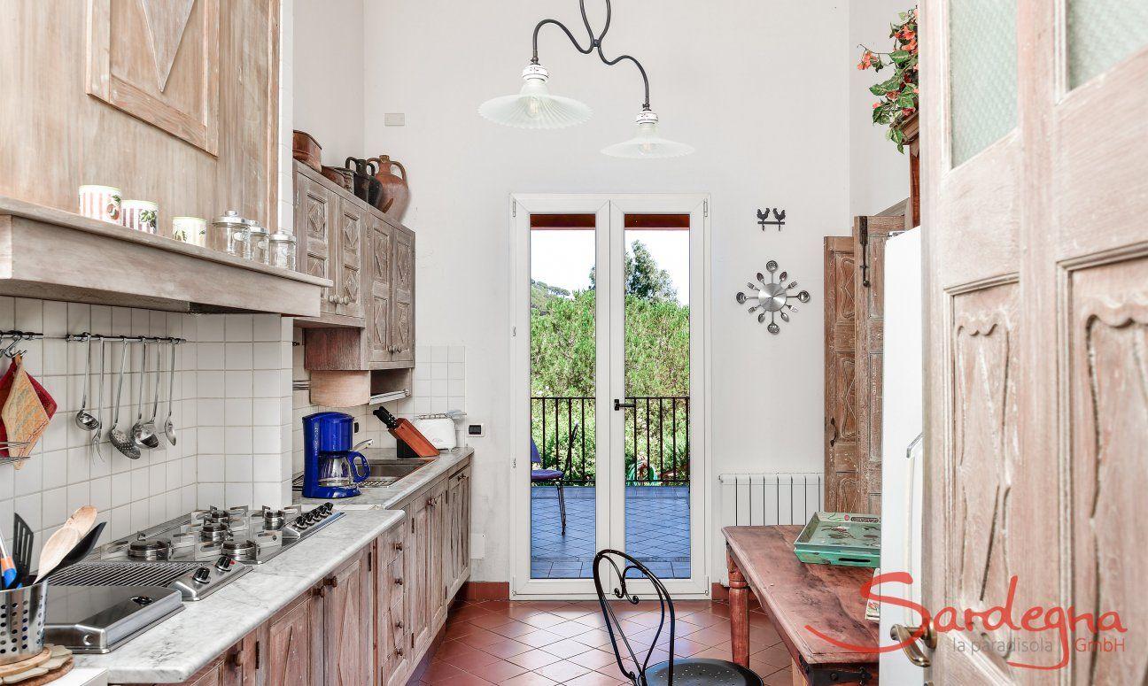 Vollausgestattete Küche mit kleinem Esstisch und Terrassenzugang
