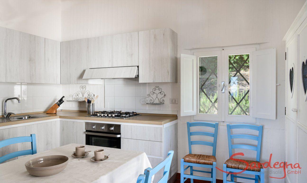 Moderne und vollausgestattete Küche mit Esstisch