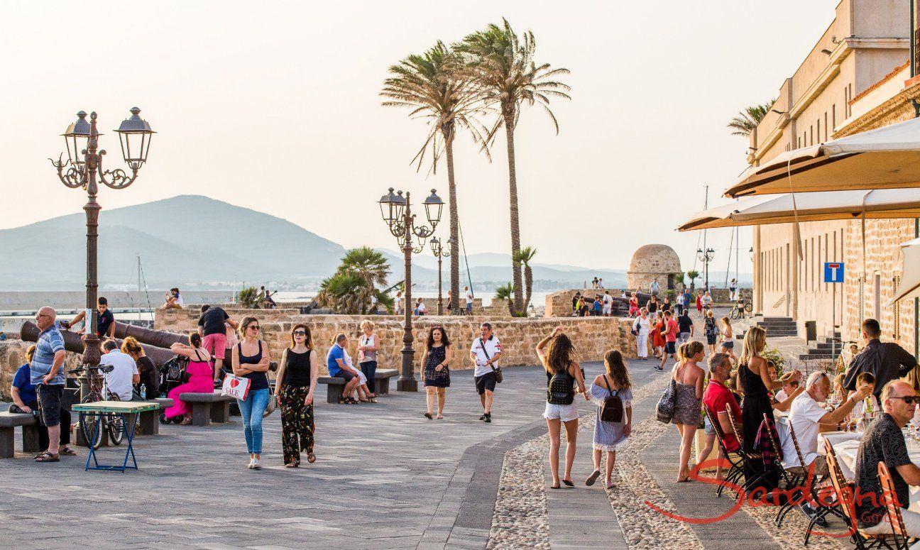 Ufermpromenade von Alghero mit alten Kanonen, hohen Palmen und Blick auf die Küste