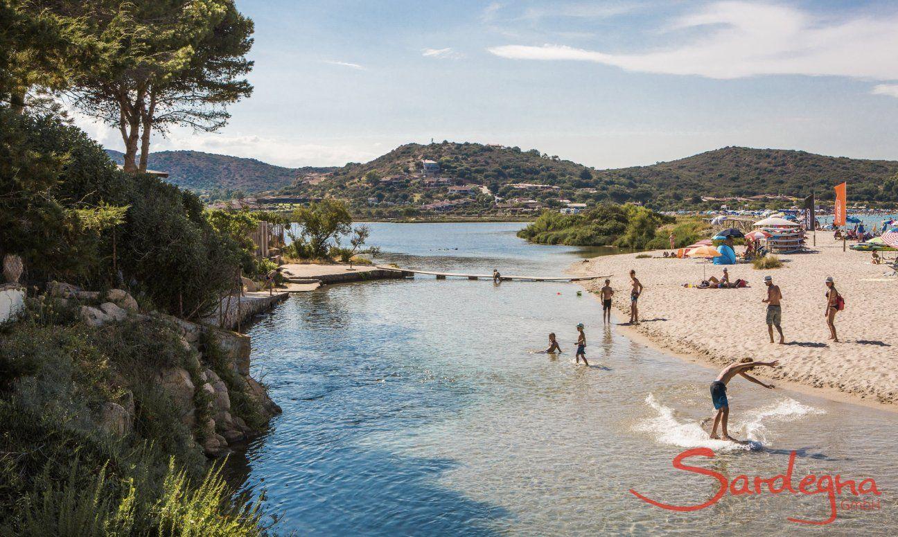 Kinder spielen im seichten Wasser der Lagune von Porto Taverna