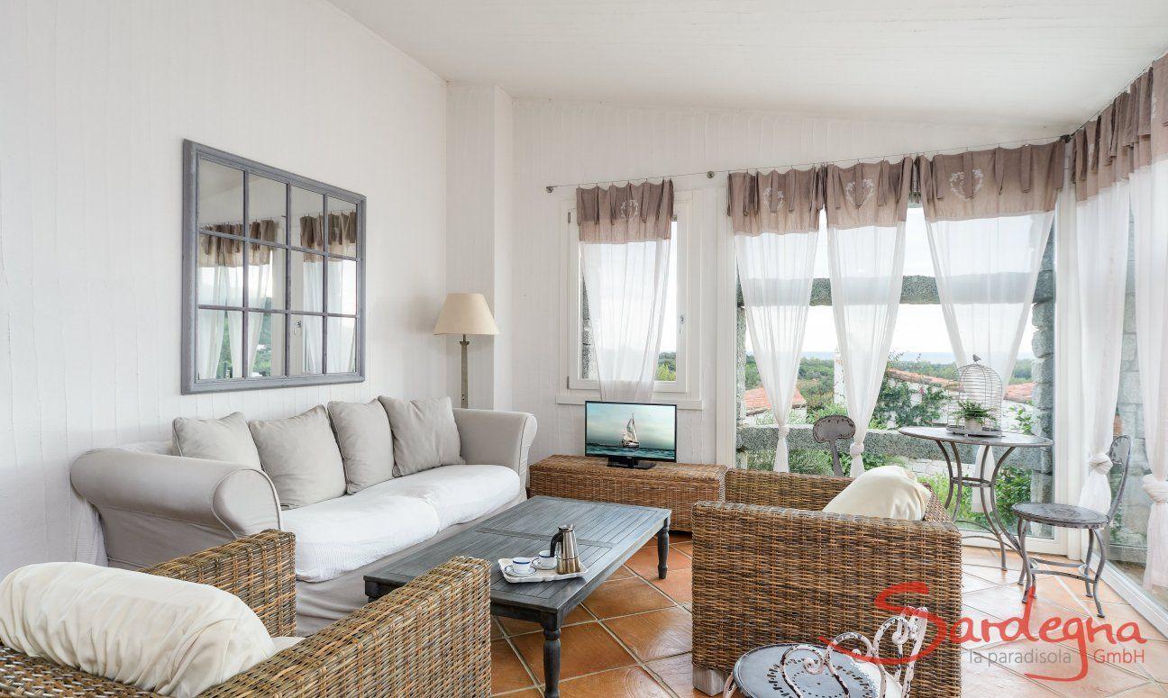 Wohnbereich mit Sofa, Sesseln und TV vor dem Panoramafenster