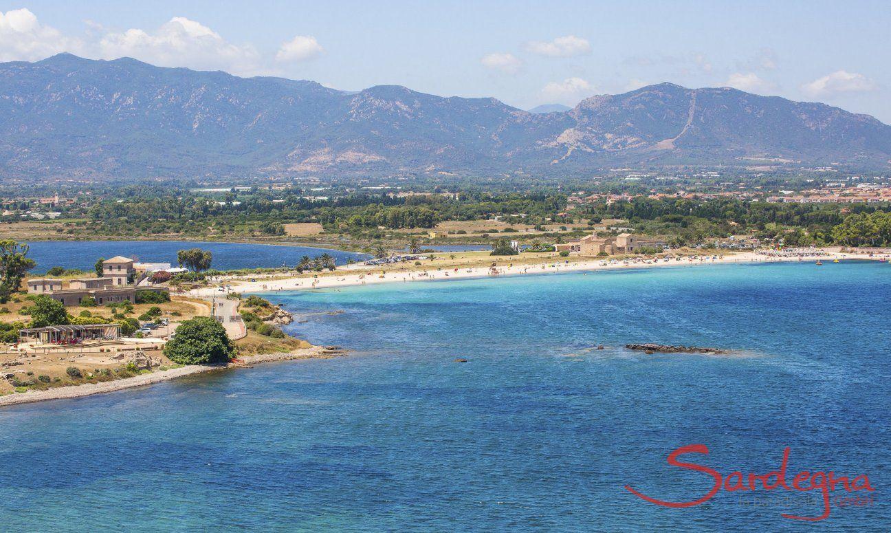 Strand von Nora mit dem Ort Pula und Bergen im Hintergrund