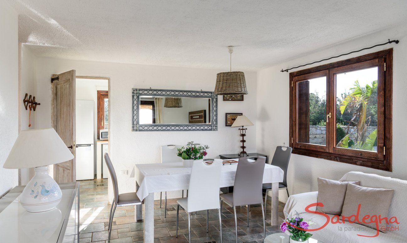 Wohnzimmer mit Esstisch und Tür zur Küche