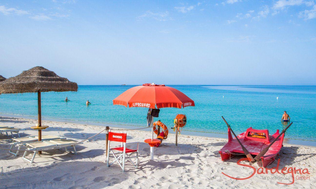 Bademeisterposten mit rotem Stuhl, Schirm und Floß am kalkweißen Strand