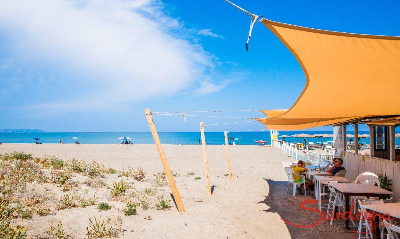 Die Snackbar Il Defino am Strand Feraxi mit schattenspendendem, gelben Sonnensegel