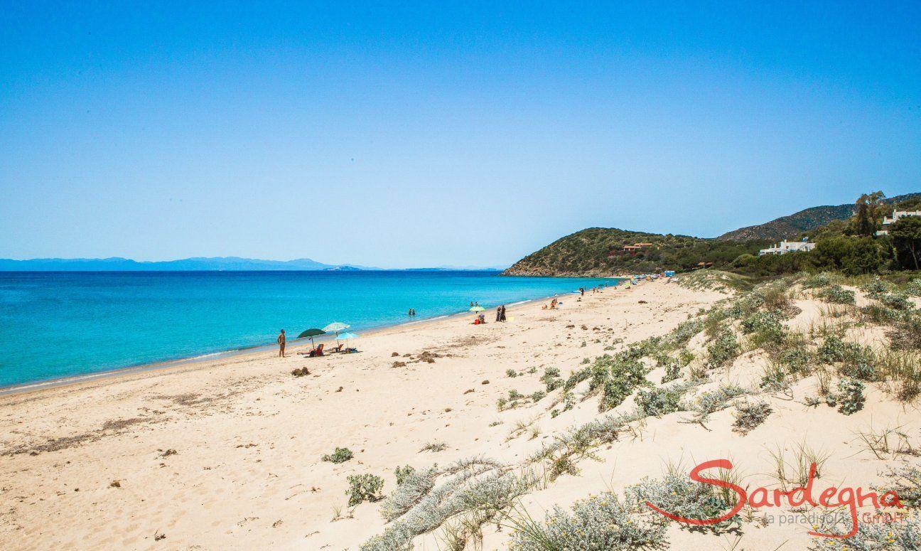 Breiter weißer Sandstrand von Geremeas mit blauem Meer und der Küste von Cagliari im Hintergrund