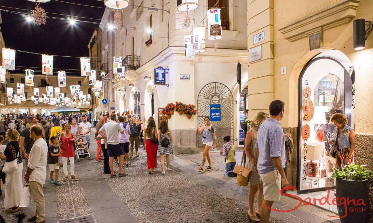 Alghero bai Nacht: mit Lanternen geschmückte Straßen voller Besucher