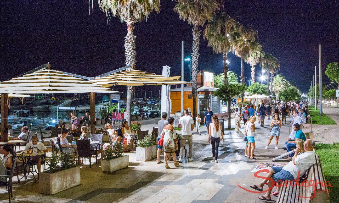 Alghero bei Nacht: Besucher flanieren and der von Lanternen erleuchteten Hafenpromenade mit hohen Palmen