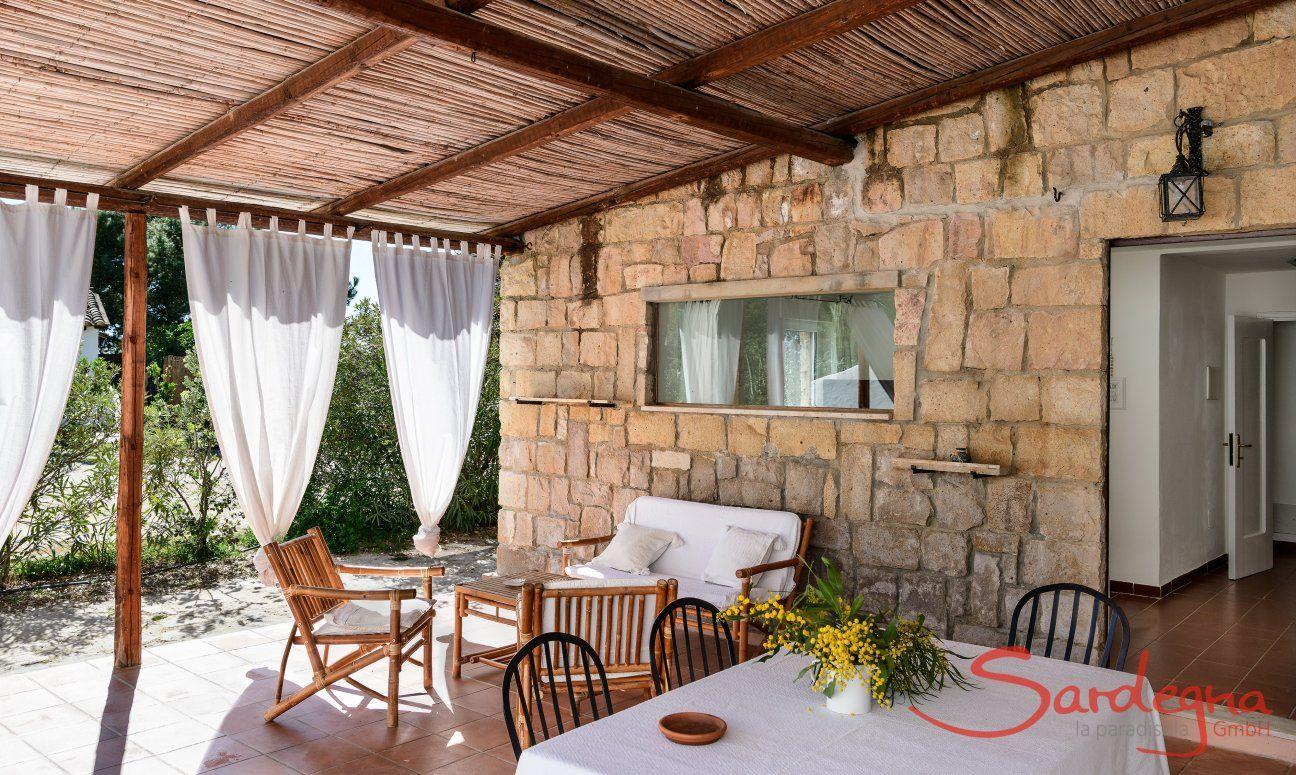Überdachte Terrasse Su Faru 3 mit Esstisch und Sofamöbeln