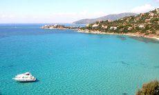 Bucht von Torre delle Stelle, auf dem durchsichtigen Meer schwimmt eine Motorjacht
