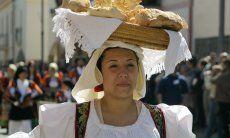 Frau in sardischer Tracht, die auf traditionelle Art einen Korb mit Festtagsbrot auf dem Kopf trägt