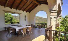 Überdachte Terrasse mit großem Esstisch und Blick in die Natur