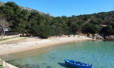 Blaues Fischerboot schwebt im glasklaren Wasser der Bucht Cala Moresca bei Golfo Aranci