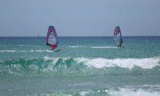 Chia | Zwei Windsurfer im glasklaren Wasser