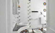 Weiß gefließtes Badezimmer mit Dusche