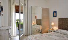 Schlafzimmer mit Doppelbett, Schrank und Terrassentür  Villa Campidano 21