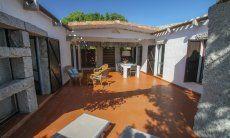Großzügige Terrasse mit Sonnenliegen und Esstisch