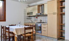 Küche unten mit großem Kühl- und Eisschrank, Ofen, Gasherd, Spülmaschine und Esstisch
