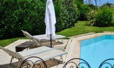 Liegen am Pool in gepflegtem Garten