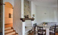 Wohnbereich mit Sofa, Esstisch und Kamin