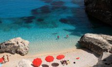 Drei rote, schattenspendende Sonnenschirme am pardiesischen Strand von Cala Goloritze; Cala Luna