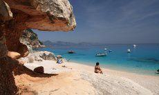 Frau sitzt am Strand vor den Felsen von Cala Luna und schaut auf die Motorboote auf dem Meer