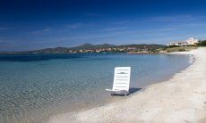 Weißer Sonnenstuhl im seichten, glasklaren Meerwasser am Strand von Golfo Aranci