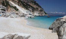 Kalkweißer Strand Cala Goloritze mit Blick auf das Meer und die steile, anschließende Küste