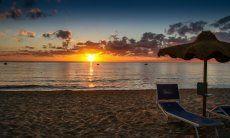 Der Sonnenaufgang über dem Meer vom Strand Cala Sinzias färbt den Horizont knallorange